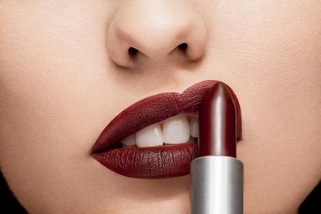 Donna che applica rossetto rosso sulle labbra in primo piano foto