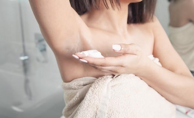 Donna che applica crema da barba sull'ascella. concetto di depilazione