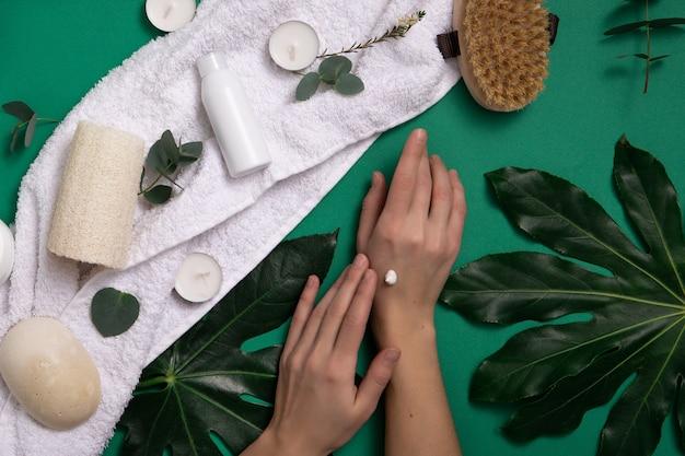 Donna che applica il trattamento della pelle vicino a asciugamani, foglie e prodotti