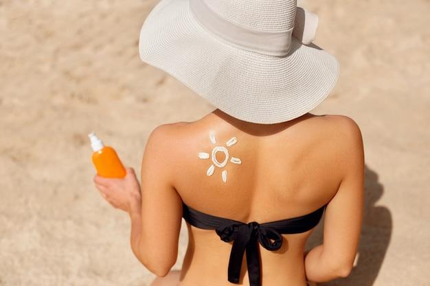 Donna che applica crema solare sulla spalla abbronzata a forma di sole.