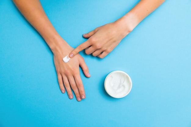 Donna che applica crema bianca sulla pelle della sua mano con il dito indice