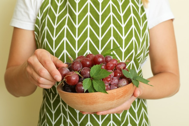 Donna in grembiule tenere ciotola con uva