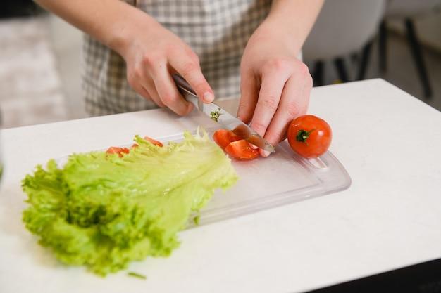 La donna in grembiule tiene il coltello e taglia i pomodori e le verdure a bordo per una sana insalatiera in cucina sullo sfondo kitchen