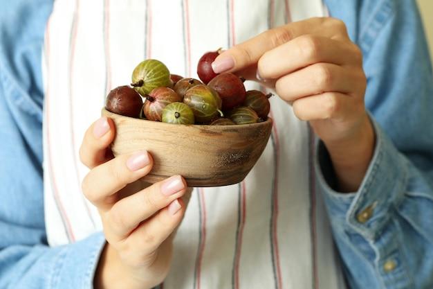 La donna in grembiule tiene una ciotola di uva spina, primo piano