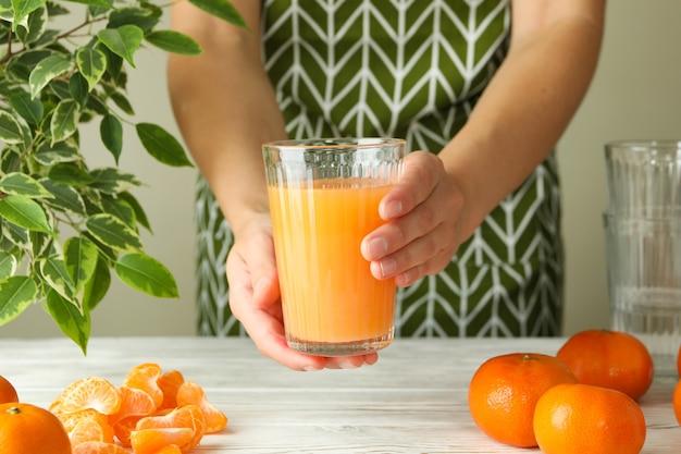 La donna in grembiule tiene il bicchiere con succo di mandarino, primo piano