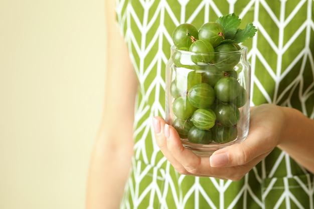 La donna in grembiule tiene un barattolo di uva spina, primo piano