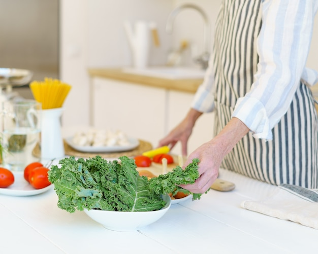 Donna in grembiule che prepara insalata di verdure mentre cucina il cibo in cucina a casa