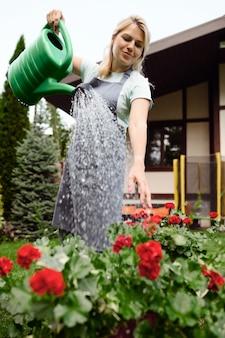 Donna in grembiule che innaffia i fiori nel giardino