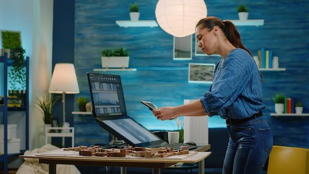 Architetto donna che analizza il modello di edificio su tablet e computer