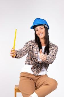 Architetto della donna in cappello duro e un metro a nastro e che mostra il pollice su a portata di mano