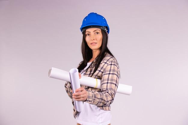 Architetto della donna in cappello duro su una priorità bassa isolata bianca con un progetto in mano esamina la macchina fotografica