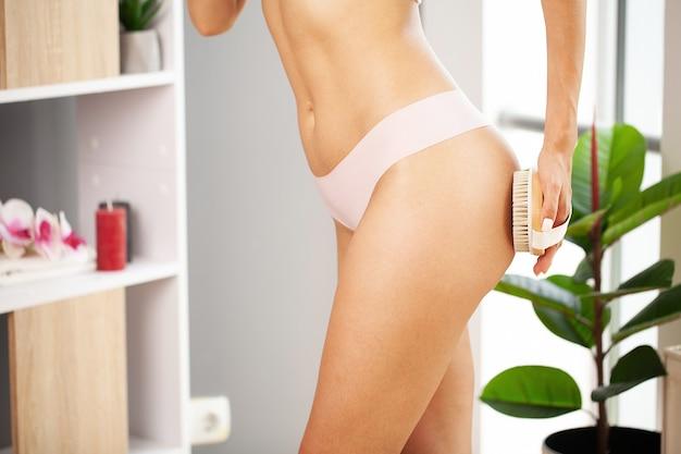 Braccio della donna che tiene il pennello asciutto sulla parte superiore della gamba, il trattamento della cellulite e la spazzolatura a secco.