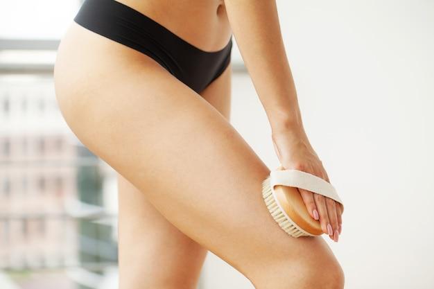 Braccio della donna che tiene la spazzola asciutta alla parte superiore della gamba, trattamento della cellulite e spazzolatura a secco.