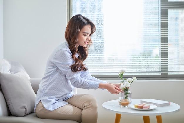 Donna disponendo lisianthus fiori in un vaso di vetro a casa.