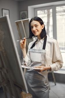 Donna in una scuola d'arte che indossa un grembiule.