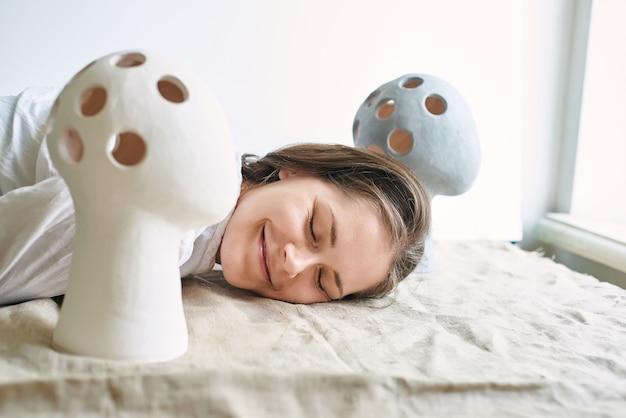 Donna artigiana ceramista sullo sfondo di vasi insoliti a forma di testa umana