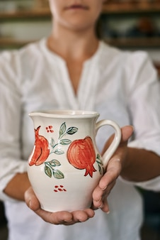 Donna artigiana ceramista che tiene in mano una bella brocca di argilla dipinta a mano
