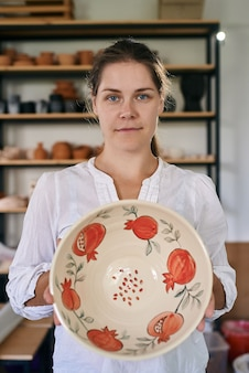 Donna artigiana ceramista che tiene in mano un bellissimo piatto di argilla dipinto a mano
