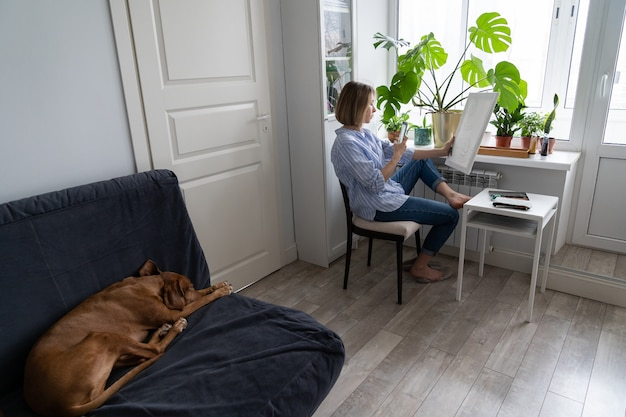 La donna artista dipinge un quadro su tela e scatta una foto su smartphone seduto vicino alla finestra di casa