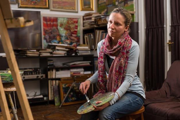 Artista donna seduta guardando la sua tela in uno studio con un pennello e una tavolozza in mano