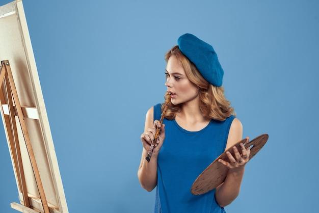 Artista della donna con la tavolozza del disegno della holding del berretto