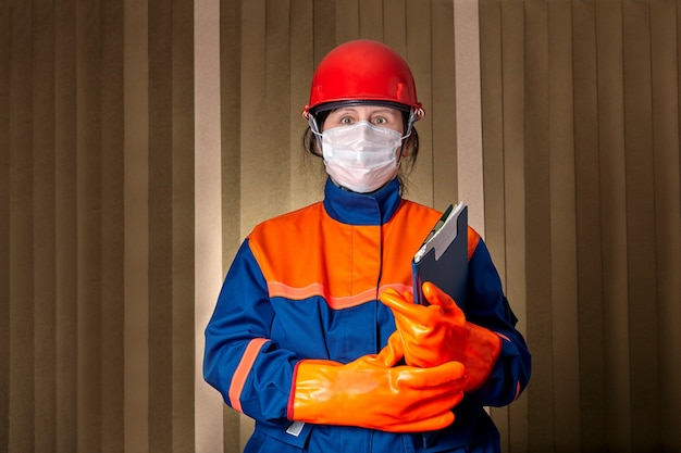 La donna come ingegnere elettrico utilizza indumenti protettivi e maschera facciale per proteggersi dagli infortuni sul lavoro e dalla pandemia covid-19 dell'infezione da coronavirus.