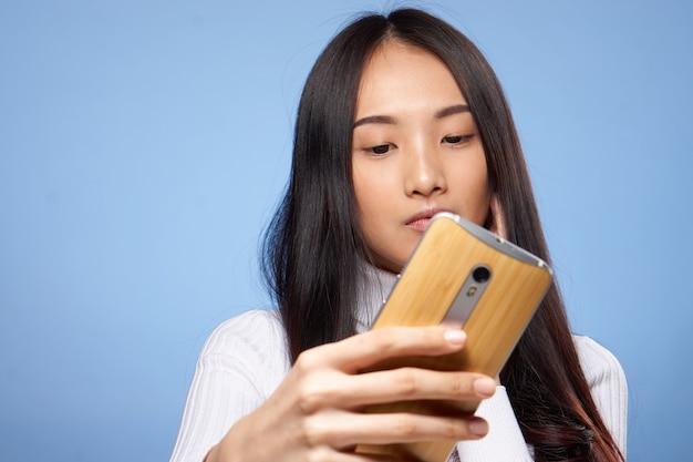 Donna di aspetto asiatico tenendo il telefono in mano la tecnologia di comunicazione internet blu