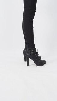 Le gambe asiatiche della donna con i pantaloni neri e il tallone sono in piedi