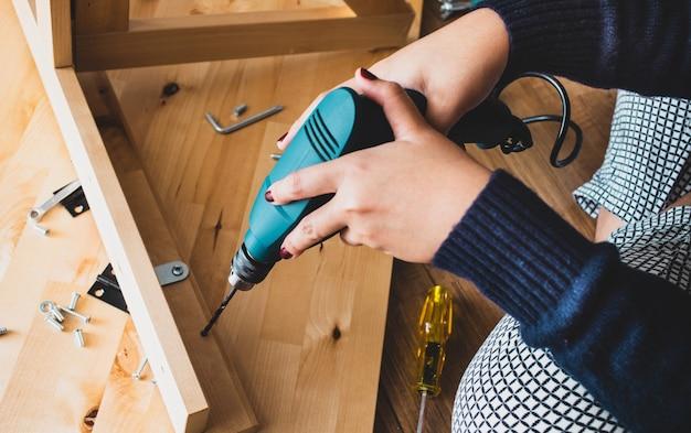 Donna montaggio mobili in legno, fissaggio o riparazione di casa con trapano.