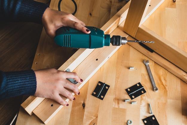 Donna montaggio mobili in legno, fissaggio o riparazione di casa con trapano