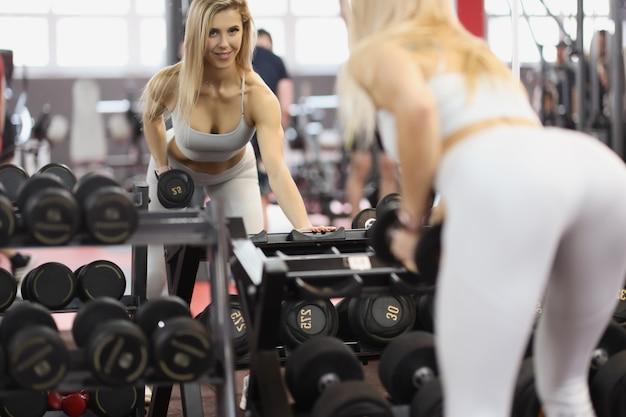 Manubrio di sollevamento dell'atleta della donna davanti allo specchio nel concetto di culturismo femminile della palestra