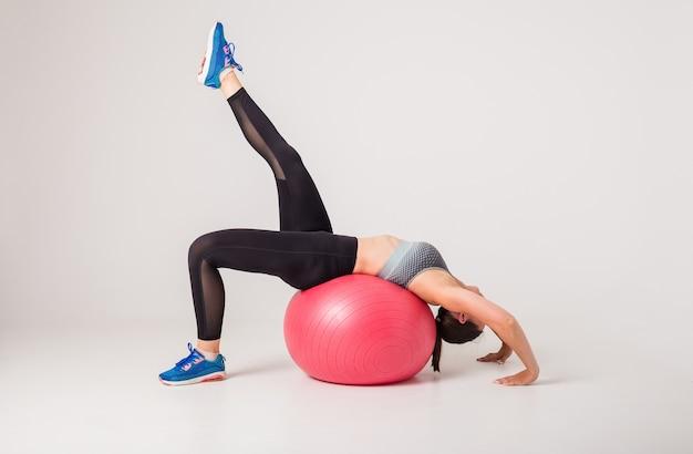 Atleta donna esegue esercizi su una palla fitness su un bianco isolato con spazio per il testo