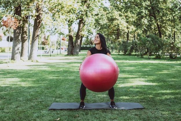 Atleta donna con una grande palla fitness si allena nel parco