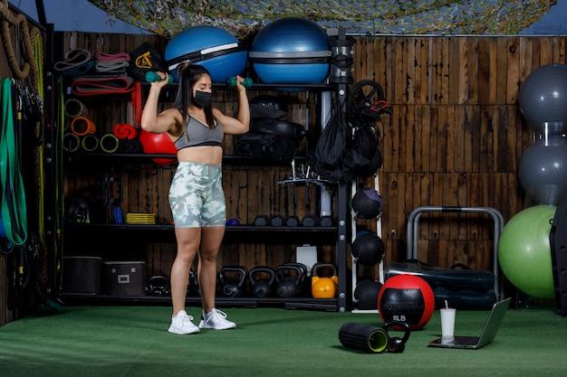 Atleta con i pesi che insegna online con un computer che indossa una maschera per la nuova normalità