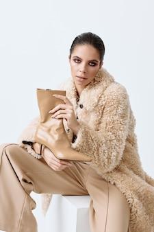 Donna in vestiti di autunno moda scarpe alla moda in studio di mano