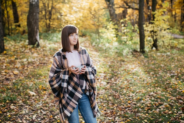 Donna nella foresta d'autunno, bere il tè da un thermos