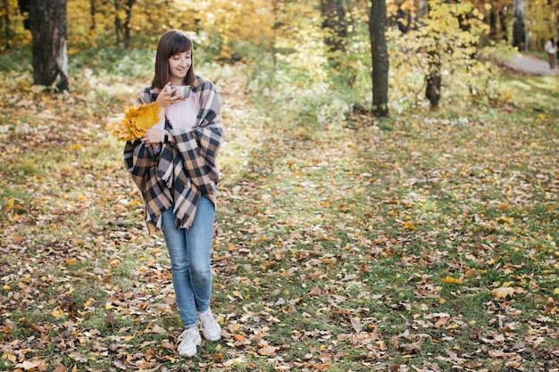 Donna nella foresta d'autunno, bere il tè con foglie in mano. sole