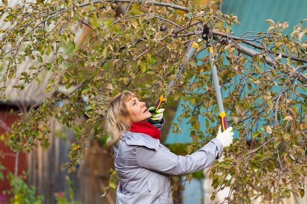 Una donna nel giardino autunnale raccoglie e rimuove la spazzatura
