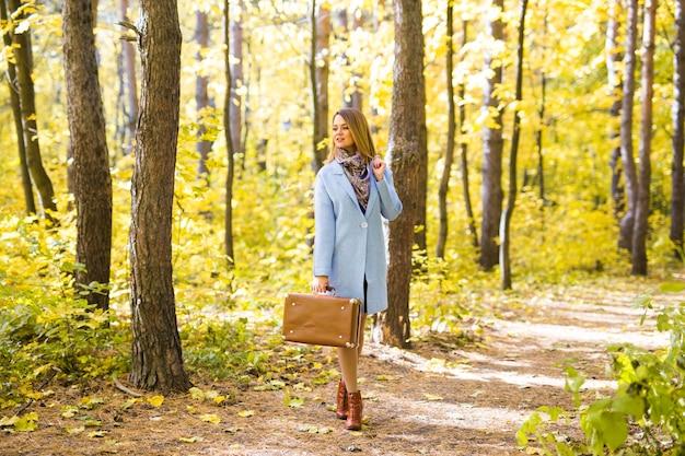 Donna nella sosta di autunno che cammina con la valigia retrò
