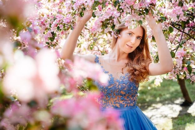 Donna su uno sfondo di mele in fiore e ciliegi ritratto di una ragazza affascinante in un vestito blu...