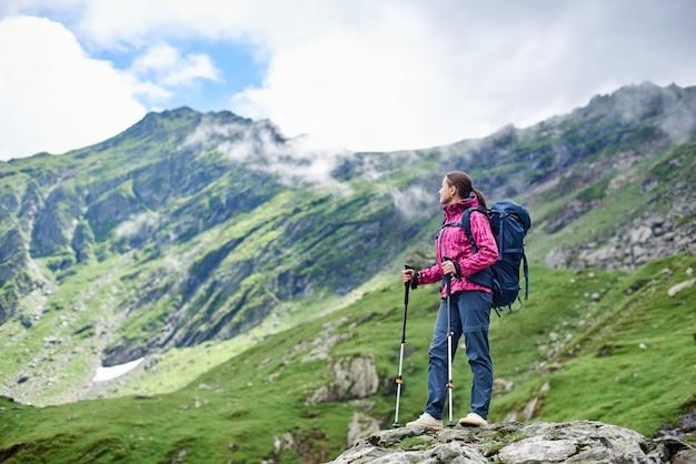 Viaggiatore con zaino e sacco a pelo della donna che riposa mentre facendo un'escursione in piedi sopra una roccia che gode del paesaggio fantastico della montagna intorno