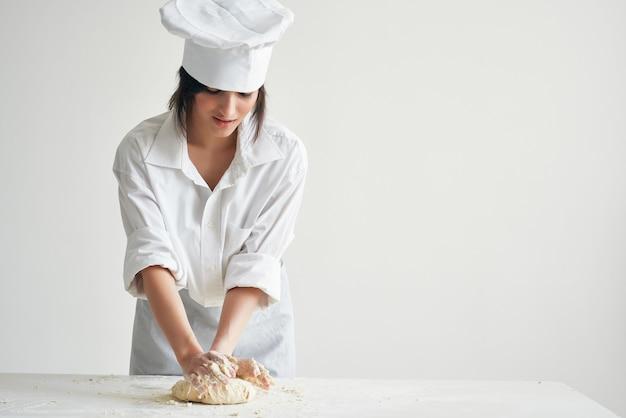 Fornaio della donna in uniforme dello chef che cucina i prodotti della farina della cucina dell'alimento