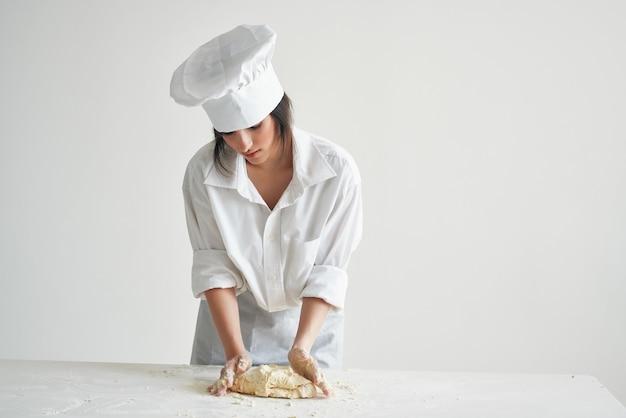 Uniforme da chef panettiere donna che prepara pasta e pasta per pizza