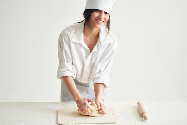 La fornaia in uniforme da lavoro stende la pasta