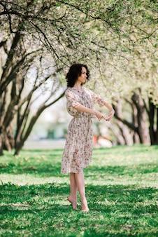 Ballerina della donna in giardino fiorito. rosa. balletto. ritratto di ragazza che balla all'aperto. moda e stile