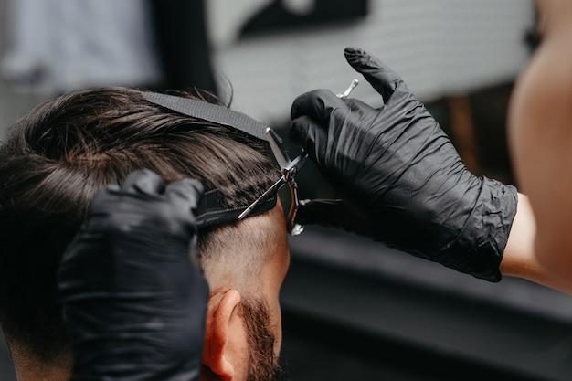 Barbiere donna che taglia i capelli a un uomo barbuto ...