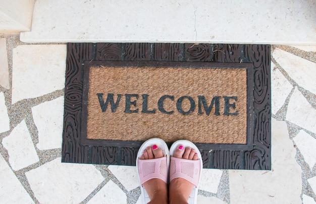Una donna a piedi nudi in piedi davanti alla porta o una nuova casa con un tappeto di benvenuto, per favore good