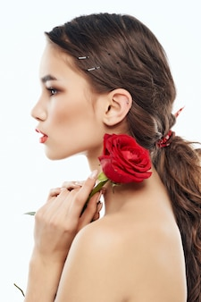 Donna spalle nude fiore rosso fascino rosso delle labbra. foto di alta qualità