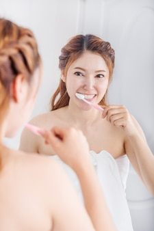 Donna in telo da bagno lavarsi i denti con specchio in bagno