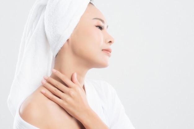 La donna in telo da bagno sta toccando il suo viso e sorridente isolato su bianco.
